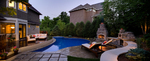 Outdoor fireplace-teak deck-custom pool and deck-creed retaining wall-small backyard-dusk photo with landscape lighting