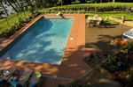 wrought iron fence-large pool-terracotta deck-large hot tub-raised planters-overlooking lake-luxury backyard landscape