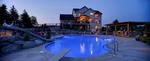 Oversized pool-whole house landscape-outdoor kitchen-diving board-boulder wall-dusk photo-luxury landscape