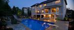 large pool-dusk-landscape lighting- diving board-pool slide-suburban setting