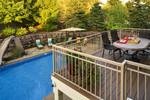 deck overlooking pool-pool-large stone retaining wall-outdoor dining-pool slide