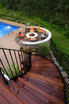 curved teak staircase-fire pit-hardscape-pavers-plantings-woods-fire-outdoor furniture